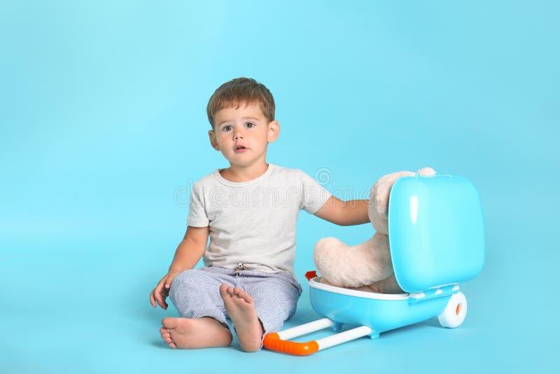 Rapaz pequeno bonito com brinquedo e mala de viagem imagem de stock