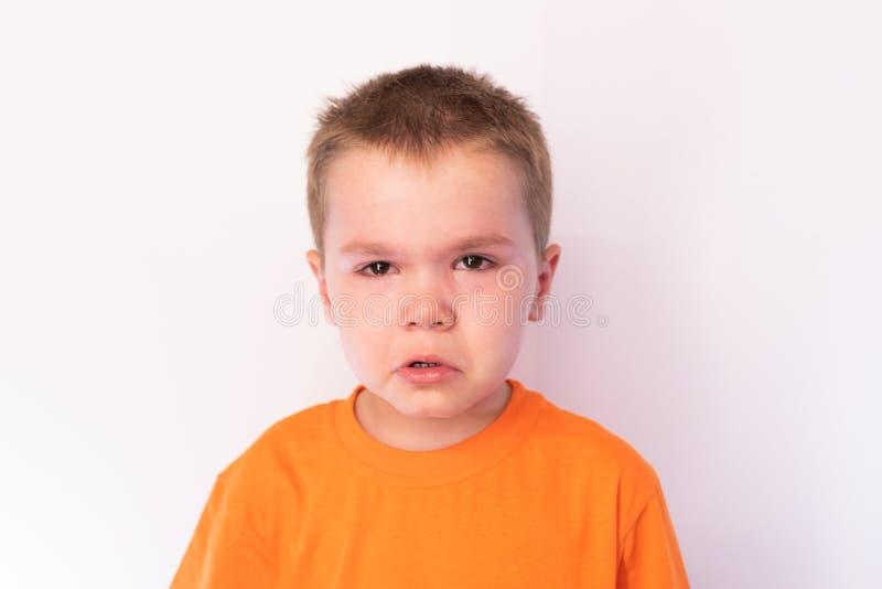 Rapaz pequeno bonito com cara triste contra um fundo brilhante fotografia de stock