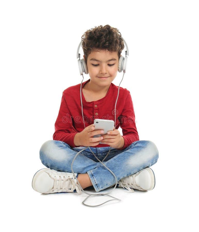 Rapaz pequeno bonito com fones de ouvido que escuta a música no fundo branco imagens de stock