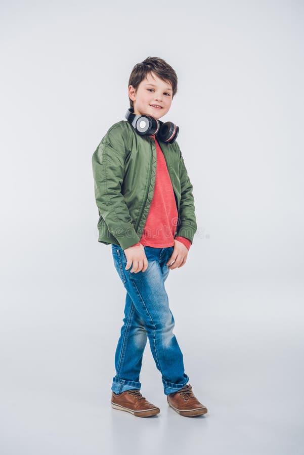 Rapaz pequeno bonito com fones de ouvido que sorri na câmera fotografia de stock royalty free
