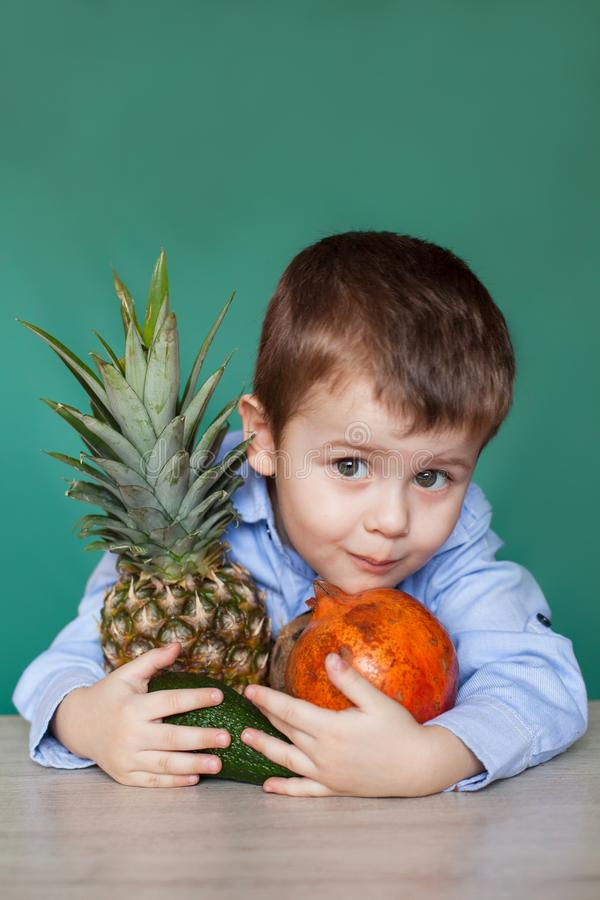 Rapaz pequeno bonito com frutos exóticos no fundo verde fotos de stock royalty free