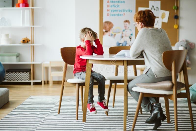 Rapaz pequeno bonito com o ADHD durante a sess?o com terapeuta profissional fotos de stock