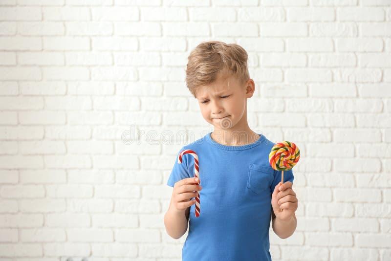 Rapaz pequeno bonito com o bastão do pirulito e de doces perto da parede de tijolo branca imagens de stock royalty free