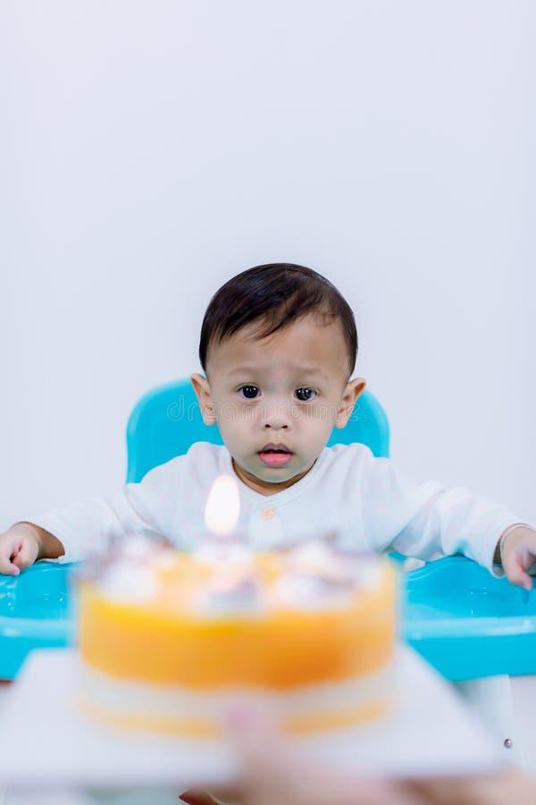 Rapaz pequeno bonito com o bolo de anivers?rio que senta-se na cadeira na sala imagem de stock
