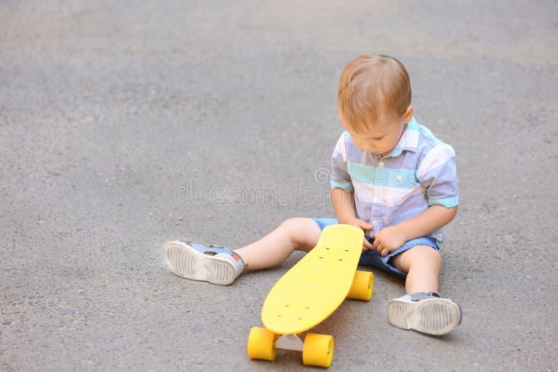 Rapaz pequeno bonito com o skate que senta-se na terra fora imagens de stock