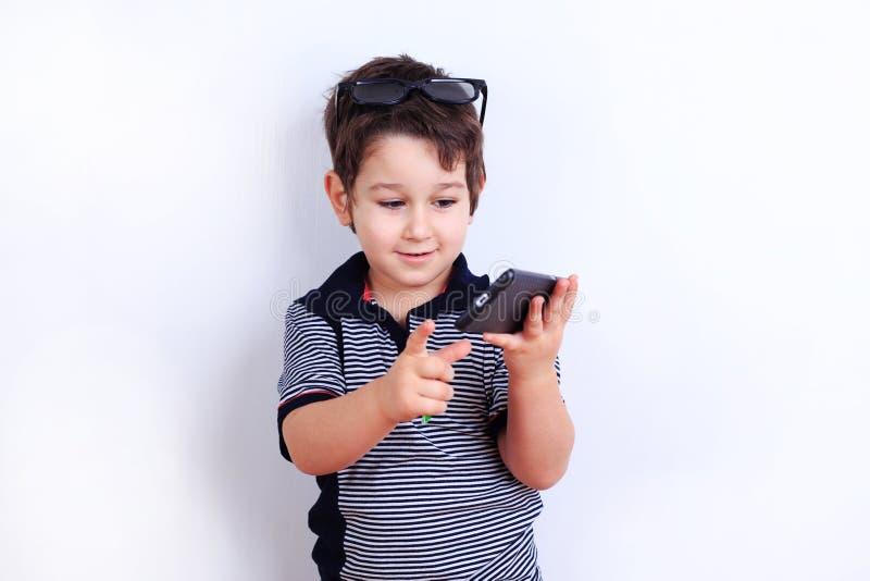 Rapaz pequeno bonito com o smartphone da tela vazia nas mãos Pasto da criança imagem de stock