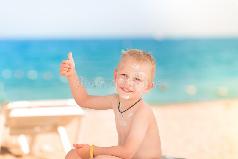 Rapaz pequeno bonito com proteção solar sobre imagens de stock