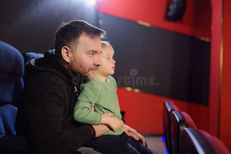 Rapaz pequeno bonito com seu filme de observação dos desenhos animados do pai no cinema imagem de stock