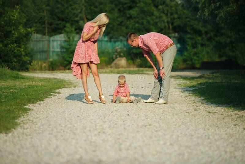 Rapaz pequeno bonito com seus pais fora imagem de stock