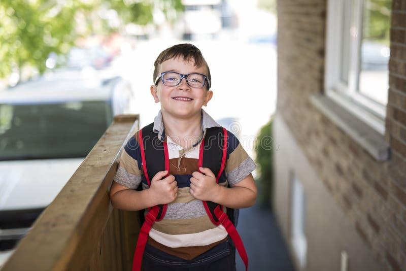 Rapaz pequeno bonito com a trouxa pronta de volta à escola imagens de stock royalty free