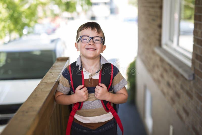Rapaz pequeno bonito com a trouxa pronta de volta à escola imagens de stock