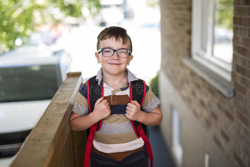 Rapaz pequeno bonito com a trouxa pronta de volta à escola foto de stock
