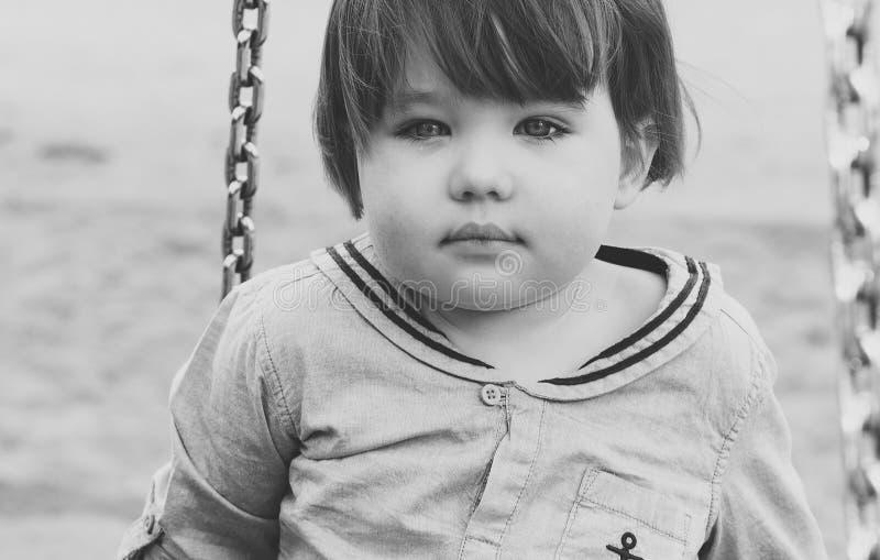 Rapaz pequeno bonito com um rasgo em seu mordente foto de stock