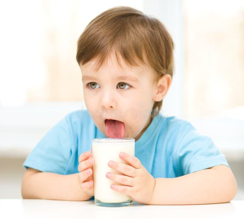 Rapaz pequeno bonito com um vidro do leite fotos de stock
