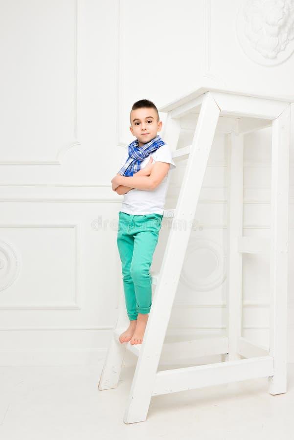 Rapaz pequeno bonito da forma em calças e t-shirt e lenço brilhantes fotografia de stock