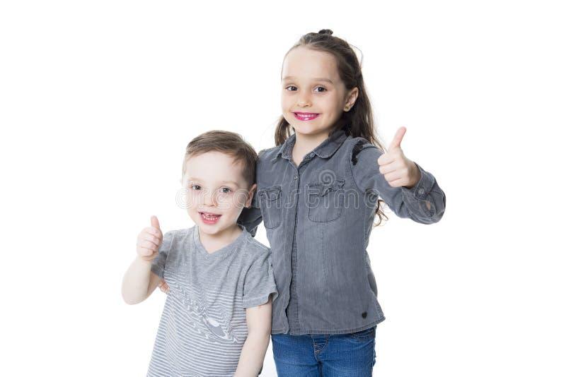 Rapaz pequeno bonito e menina com seu polegar acima no fundo branco imagem de stock