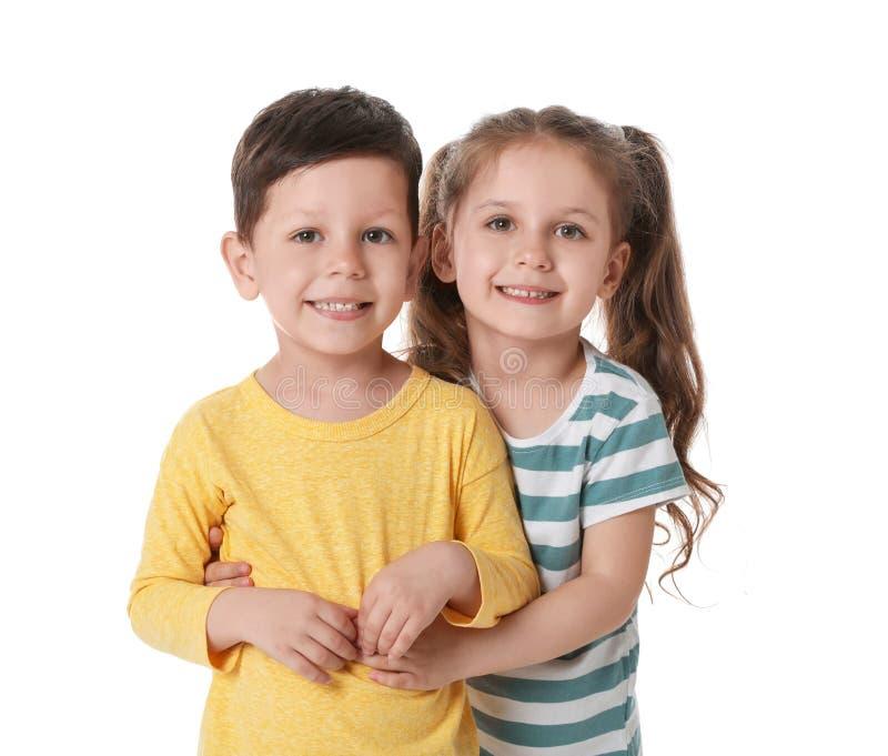 Rapaz pequeno bonito e menina que abraçam no branco fotografia de stock royalty free