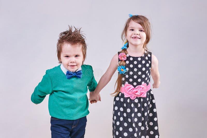 Rapaz pequeno bonito e menina que guardam as mãos fotografia de stock royalty free
