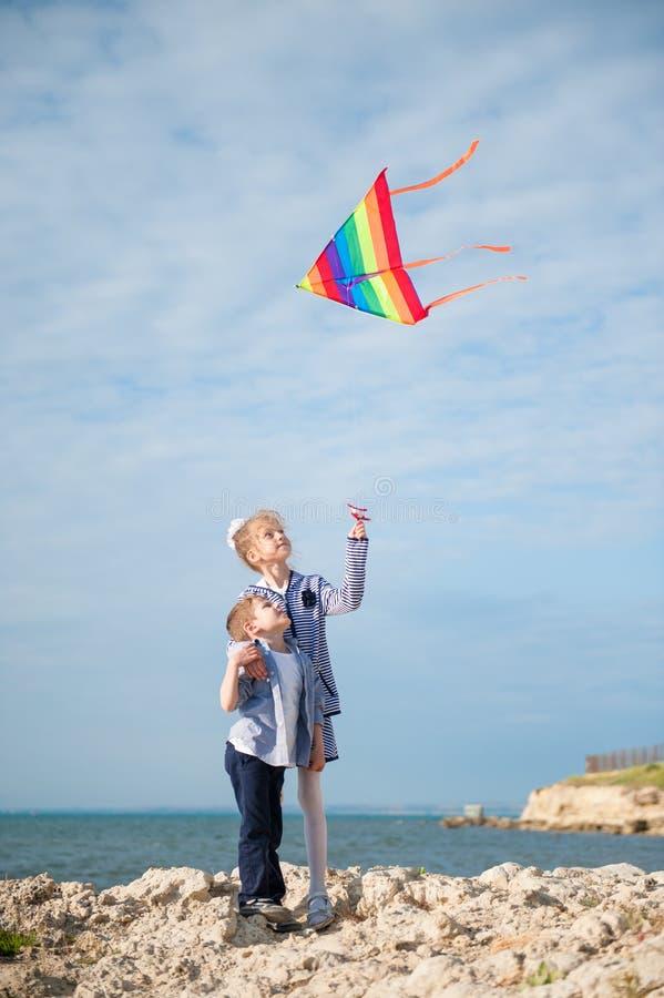 Rapaz pequeno bonito e menina que jogam com o papagaio do voo no backgroung do mar no verão fotografia de stock royalty free