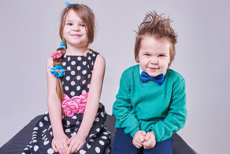 Rapaz pequeno bonito e menina que sorriem, com expressões faciais engraçadas fotos de stock