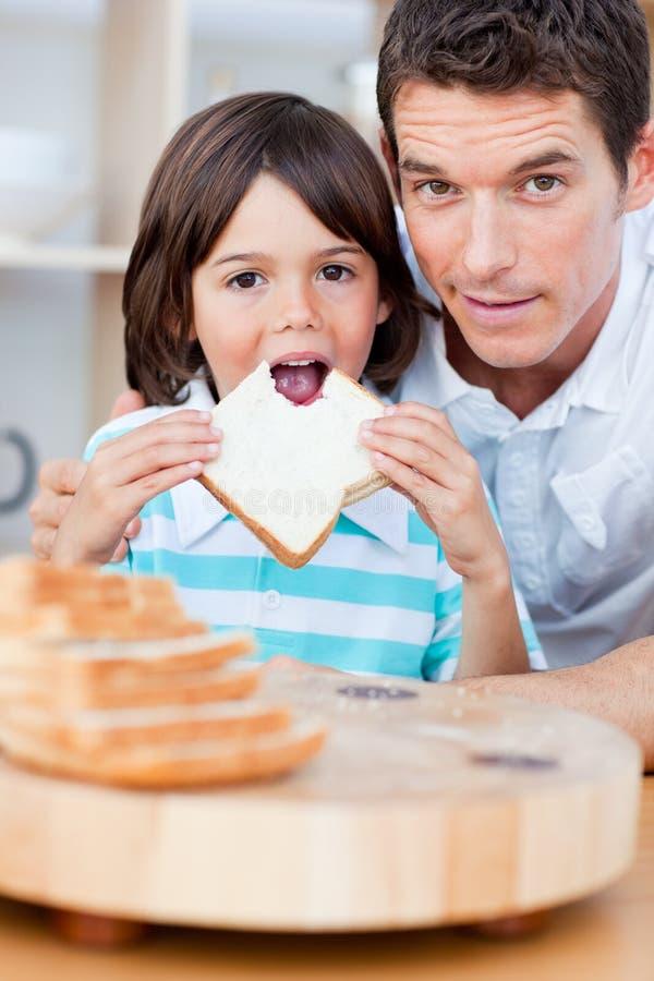 Rapaz pequeno bonito e seu pai que comem o pão foto de stock
