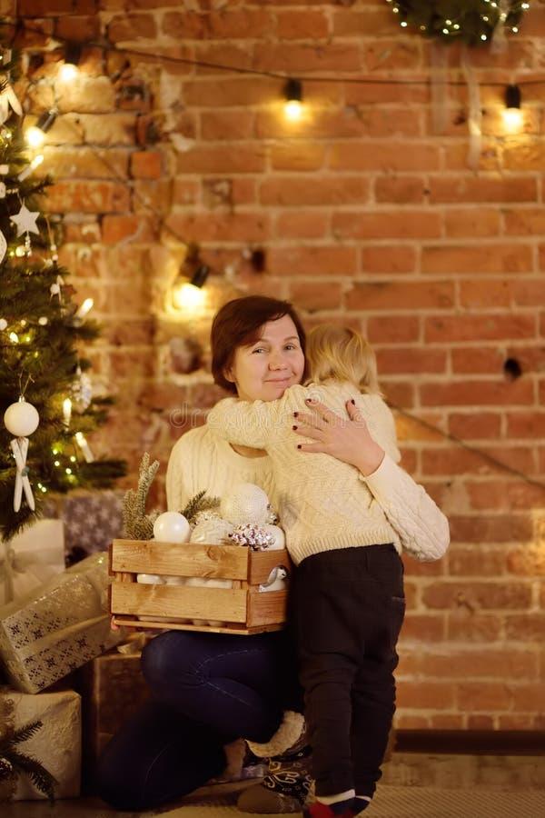 Rapaz pequeno bonito e sua mãe ou avó na Noite de Natal fotos de stock