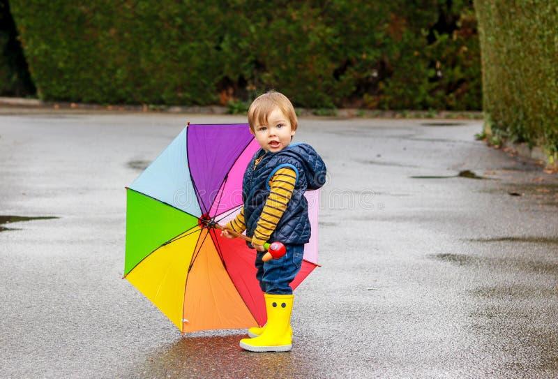 Rapaz pequeno bonito em botas de borracha amarelas com o guarda-chuva colorido do arco-íris que fica na estrada molhada que olha  imagem de stock