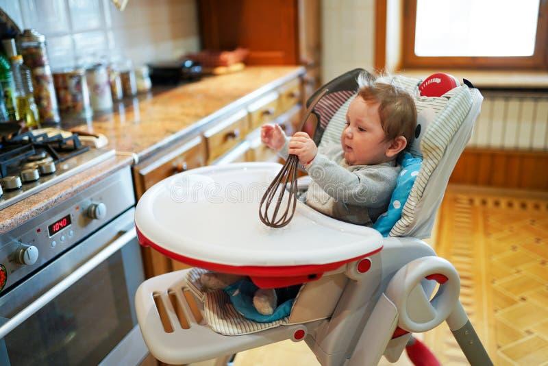 Rapaz pequeno bonito, jogando o assento na cadeira em uma cozinha viva ensolarada, bebê que sorri felizmente fotografia de stock royalty free