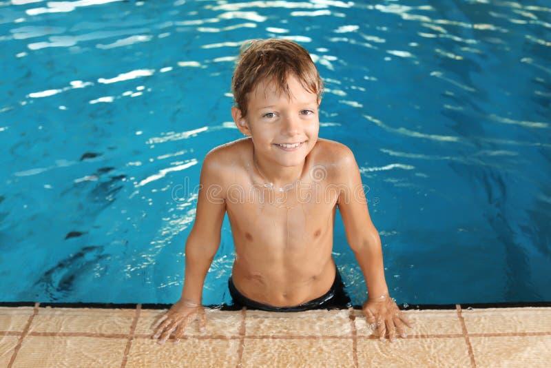 Rapaz pequeno bonito na piscina interior imagem de stock royalty free