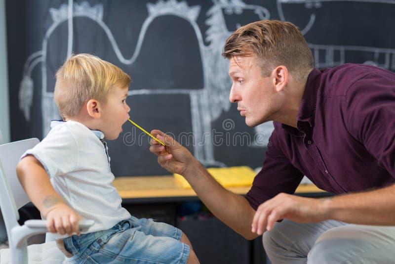 Rapaz pequeno bonito na sessão do speechtherapist imagens de stock