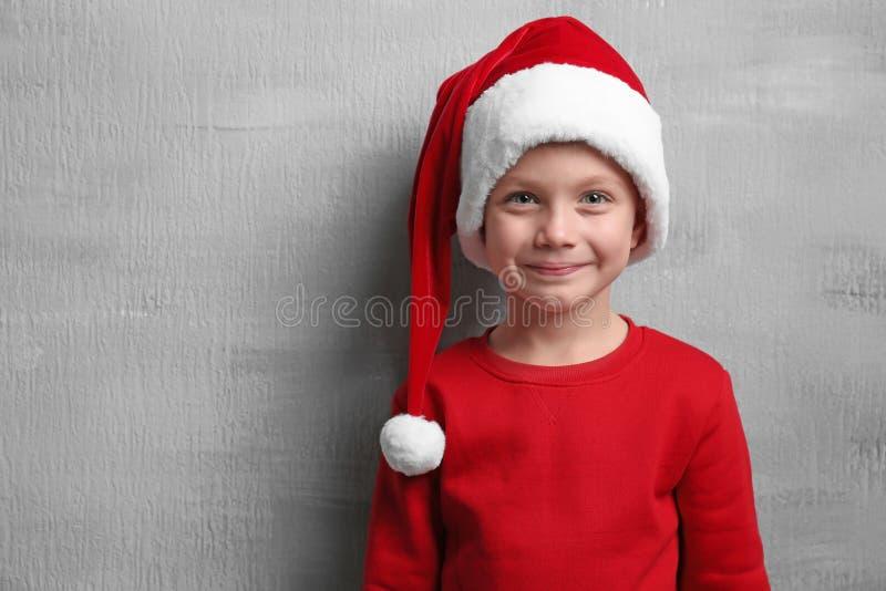 Rapaz pequeno bonito no chapéu de Santa no fundo da cor foto de stock royalty free