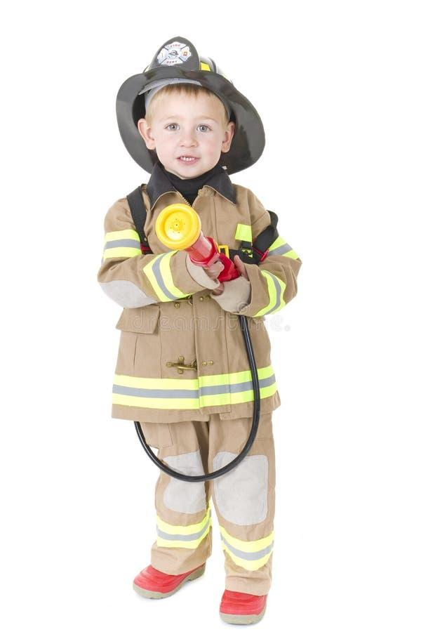 Rapaz pequeno bonito no equipamento do bombeiro imagem de stock royalty free
