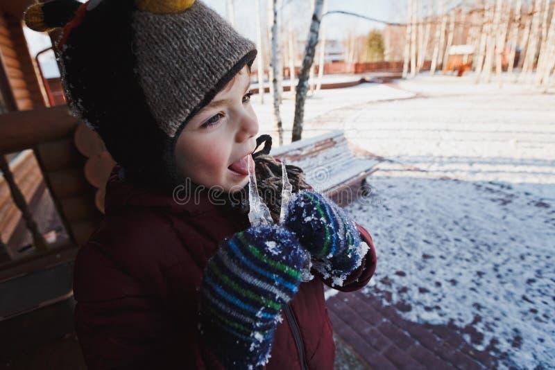Rapaz pequeno bonito no revestimento, no chapéu do inverno e nos mitenes lambendo sincelos Uma casa de madeira Paisagem do invern fotografia de stock royalty free