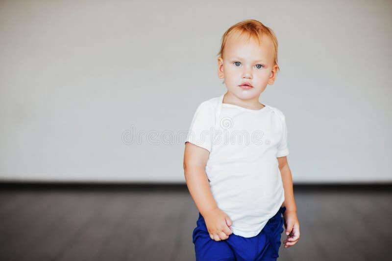 Rapaz pequeno bonito no t-shirt branco que levanta na frente do concr do grunge fotografia de stock royalty free