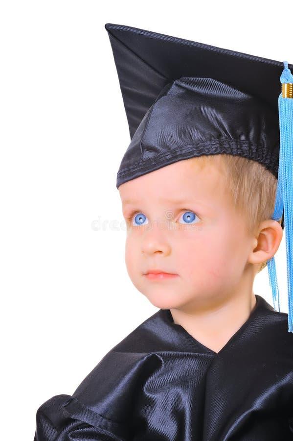 Rapaz pequeno bonito no tampão da graduação fotografia de stock