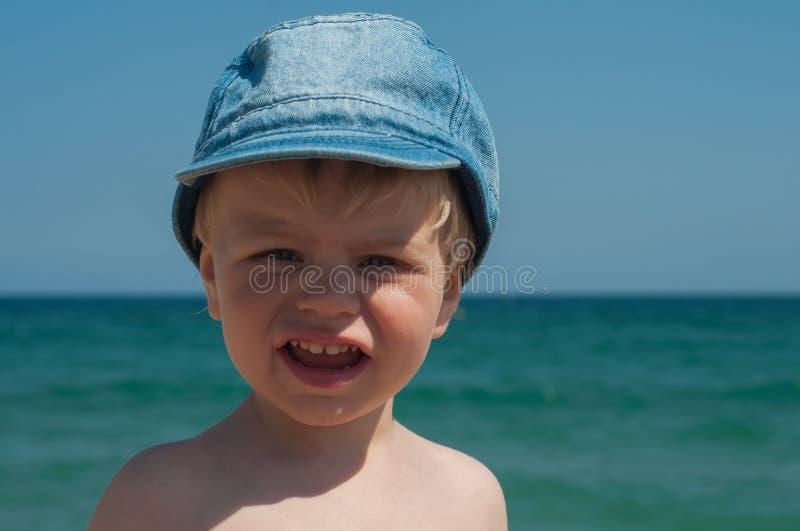 Rapaz pequeno bonito no tampão da sarja de Nimes foto de stock