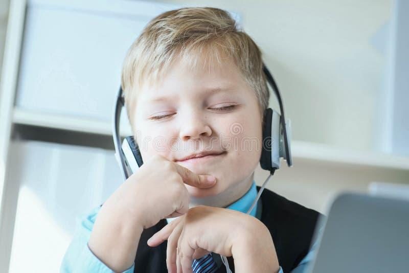 Rapaz pequeno bonito no terno que escuta a música ou o curso audio em fones de ouvido no fundo do escritório fotos de stock royalty free