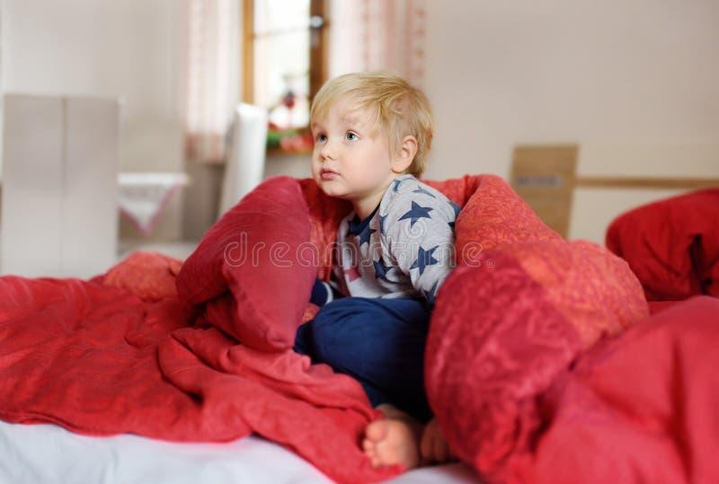 Rapaz pequeno bonito nos pijamas que têm o divertimento na cama após o sono e a observação da tevê ou o sonho foto de stock