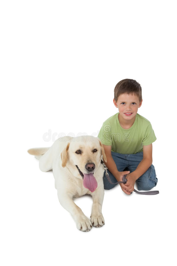 Rapaz pequeno bonito que ajoelha-se com seu cão de Labrador que sorri na câmera imagem de stock