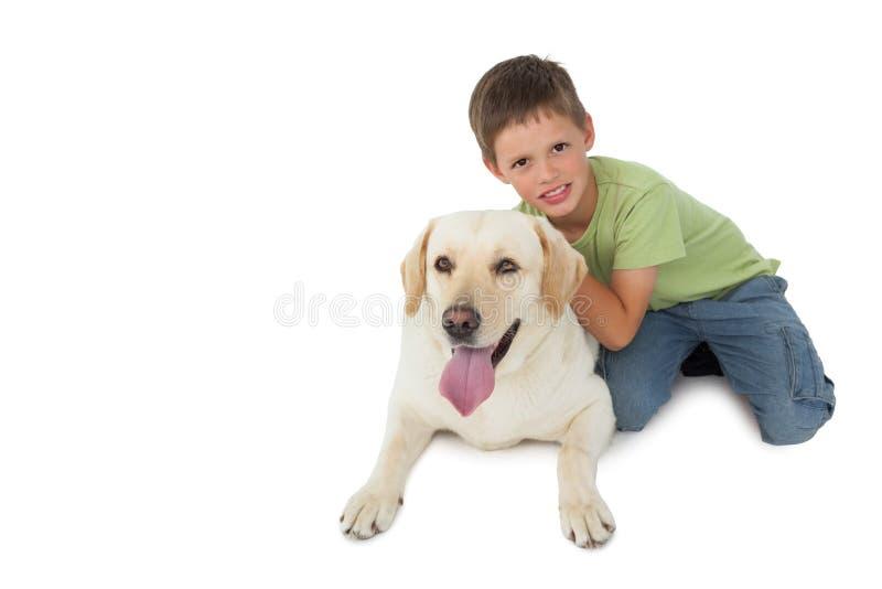 Rapaz pequeno bonito que ajoelha-se com seu Labrador que sorri na câmera foto de stock royalty free