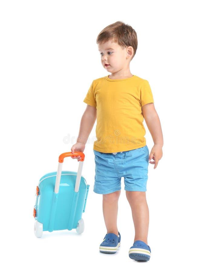 Rapaz pequeno bonito que anda com mala de viagem azul imagem de stock royalty free