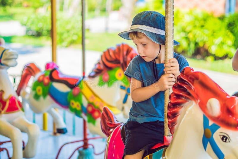 Rapaz pequeno bonito que aprecia no funfair e que monta na casa colorida do carrossel fotografia de stock royalty free