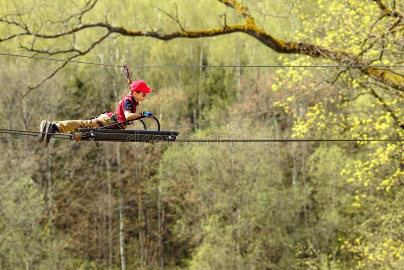 Rapaz pequeno bonito que aprecia seu tempo no parque de escalada da aventura fotografia de stock