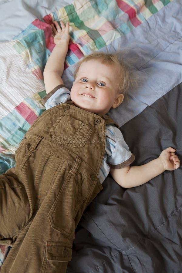 Rapaz pequeno bonito que coloca na cama fotos de stock royalty free