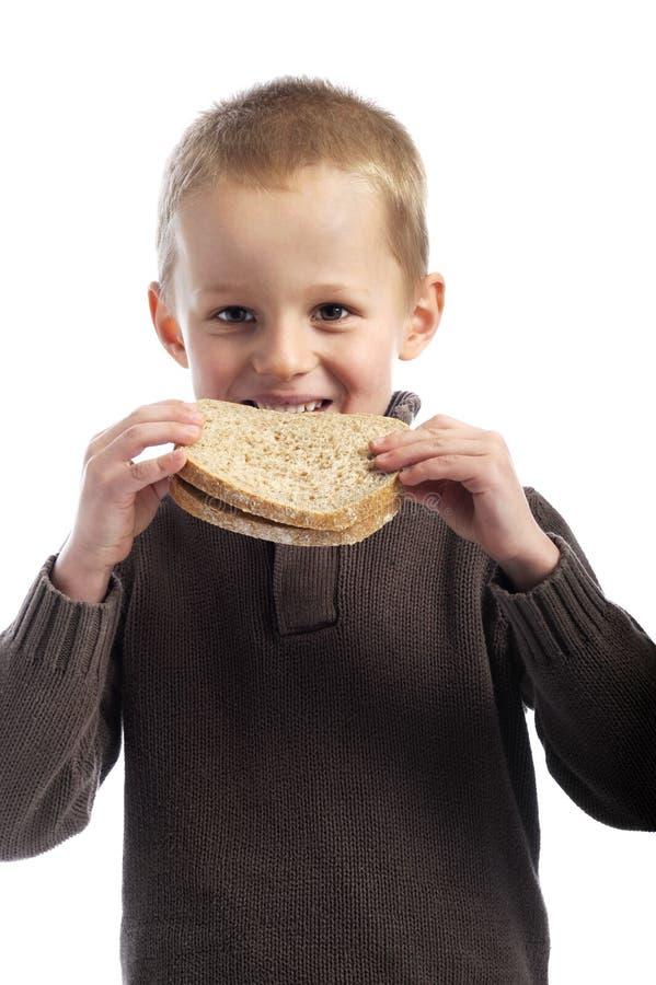Rapaz pequeno bonito que come fatias de pão imagem de stock royalty free