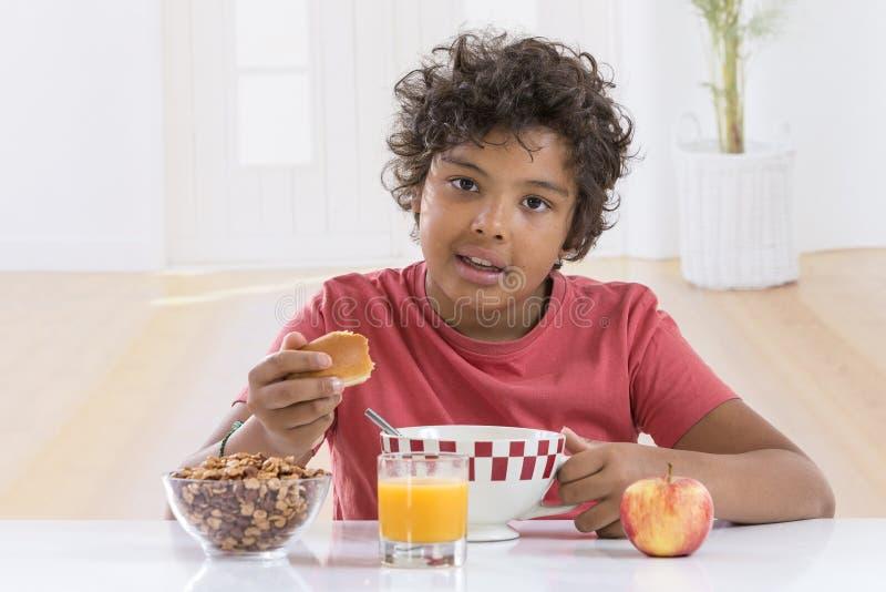 Rapaz pequeno bonito que come o café da manhã em casa que bebe uma grande bacia de leite no t-shirt do lblue foto de stock
