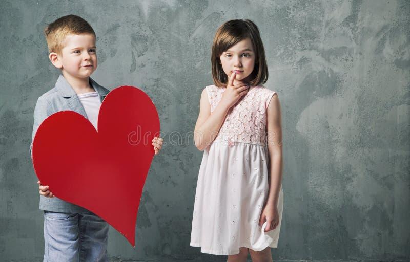 Rapaz pequeno bonito que dá um coração a sua irmã imagem de stock royalty free