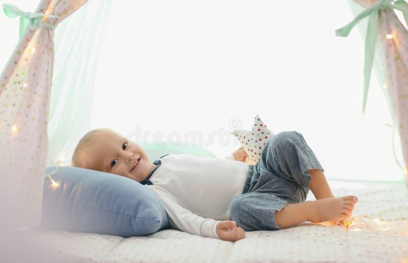 Rapaz pequeno bonito que descansa na barraca do jogo foto de stock royalty free
