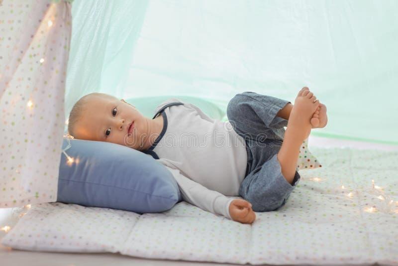Rapaz pequeno bonito que descansa na barraca do jogo foto de stock
