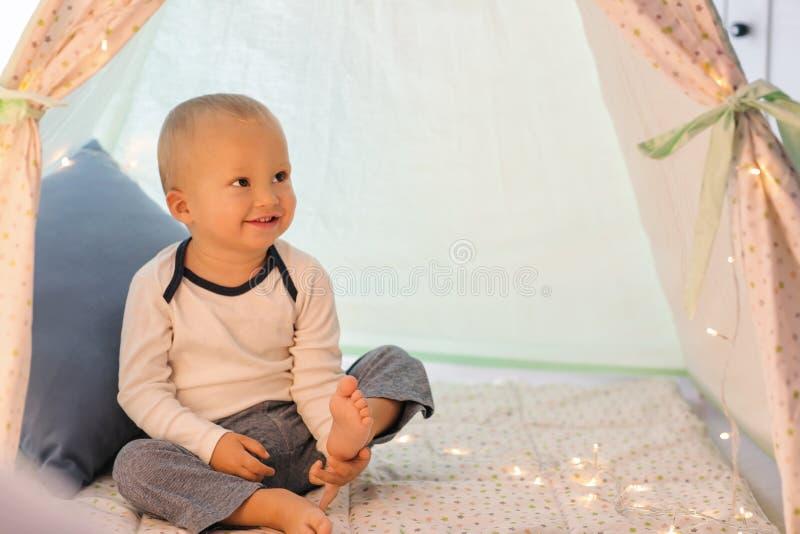 Rapaz pequeno bonito que descansa na barraca do jogo fotografia de stock royalty free